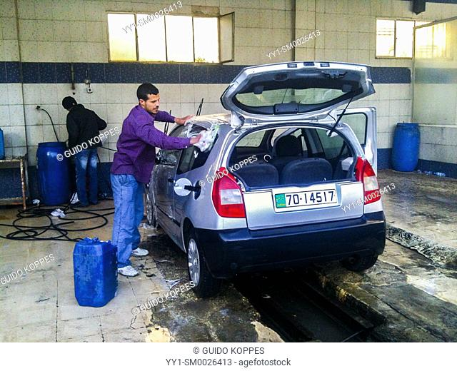 Amman, Jordan, Young adult male washing up a rental car, after driving two weeks in the dessert between the capitol and a refugee camp for a documentary photo...