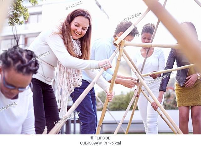 Colleagues in team building task building wooden structure smiling