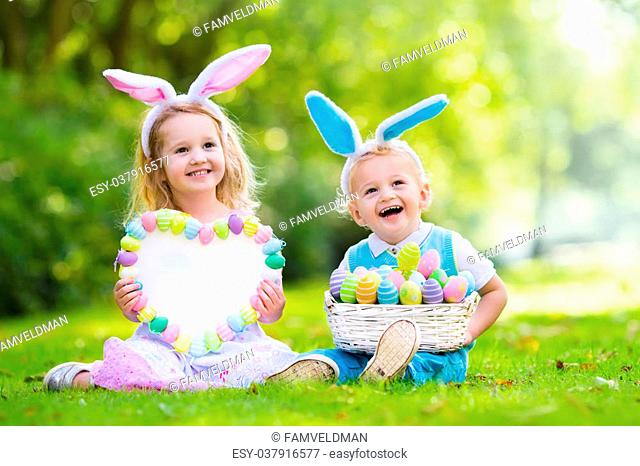 Little boy and girl having fun on Easter egg hunt. Kids in bunny ears and rabbit costume. Children with colorful eggs in a basket