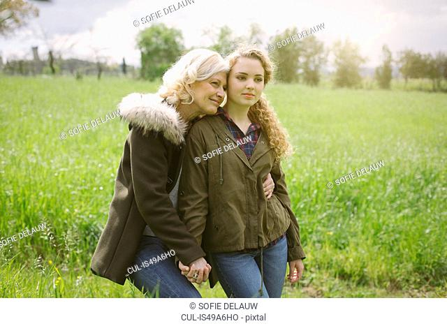 Portrait of mother and teenage daughter holding hands in field