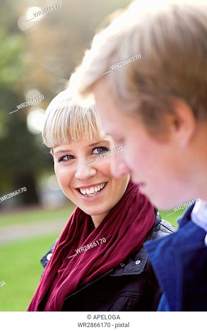 Happy woman looking at male friend in university campus