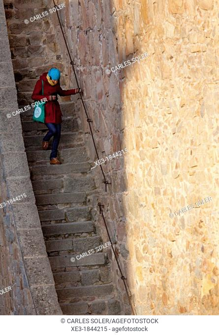 Tourist going down the stairs of the Chemin de ronde (walkway), City Wall, Avila, Spain