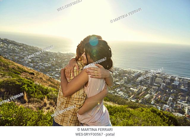 South Africa, Cape Town, Signal Hill, two young women hugging above the city