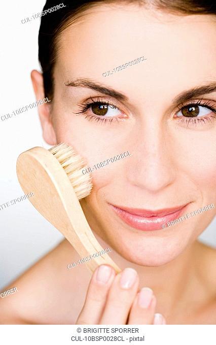 Woman brush massage her face