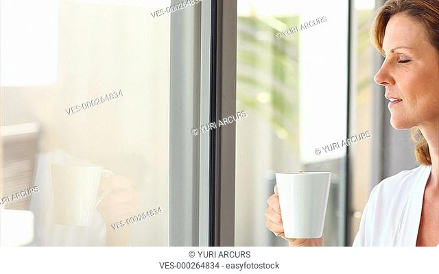 Pretty mature woman has a cup of coffee in the morning and looks forward to a new day