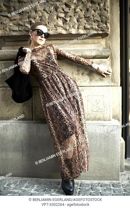 fashionable woman leaning on wall, in Munich, Germany