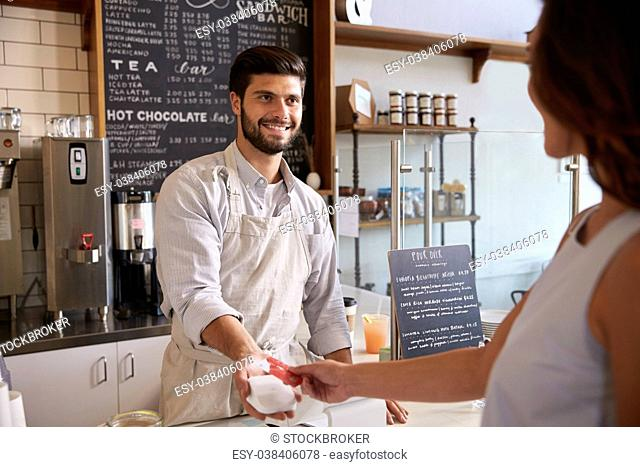 Barista taking card payment from a customer at a coffee shop