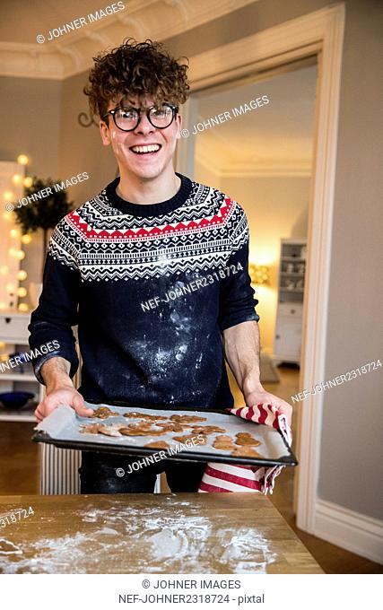 Young man baking gingerbread cookies