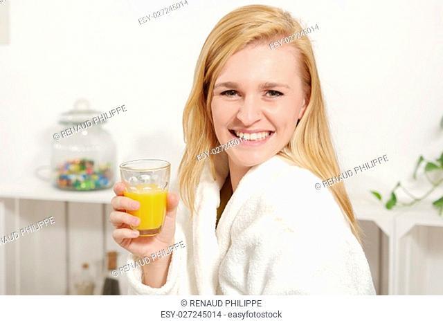 beautiful young blonde woman drinking orange juice in morning