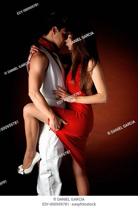 Young couple dancing embrace passion romance on dark red light background