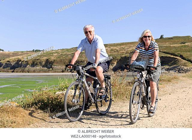 France, Bretagne, Finistere, Senior couple on e-bikes at the coast