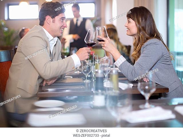 Couple clinking wine glasses in restaurant