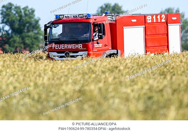 24 June 2019, Mecklenburg-Western Pomerania, Nossentiner Hütte: Firefighters drive their emergency vehicle near one of the crash sites through a field near...