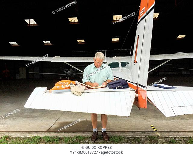 Seppe Airfield, Oudenbosch, Netherlands. Private pilot filing his airplane log book after completing a flight with his single prof Cessna airplane