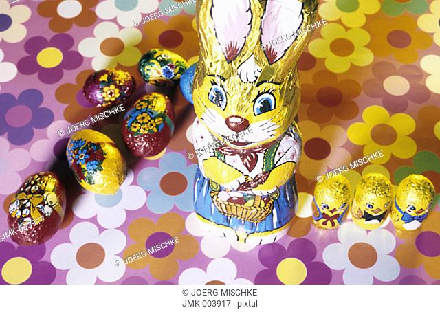 A chocolate Easter bunny and chocolate Easter eggs on a coloured ground