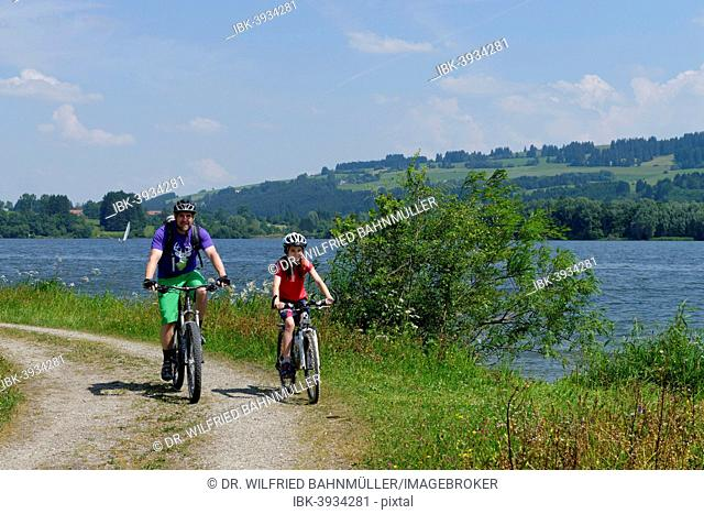 Father and child on a bike tour at Rottachspeicher reservoir, Rottachsee Lake, Oberallgäu, Swabia, Bavaria, Germany