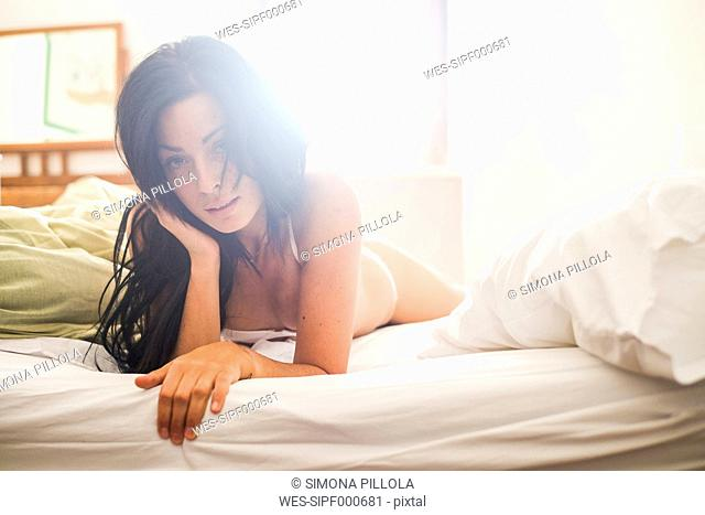 Woman lying on bed, against sunlight