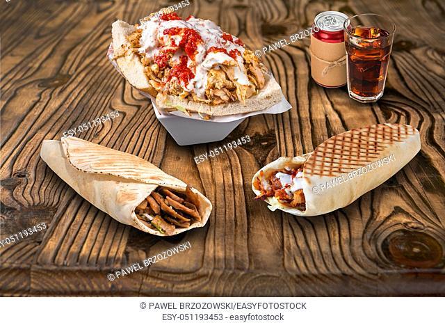 Doner kebab, pita sandwiches and cola on wooden background. For fast food restaurant design or fast food menu