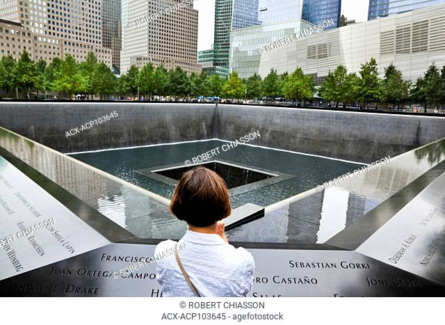 Woman at the corner of a one-acre pool and below-ground level waterfall on the site of the 9/11 Memorial. New York City, New York, U.S.A