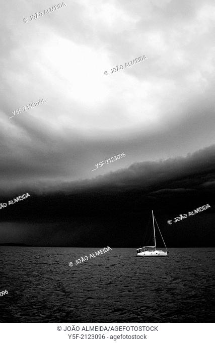 Anchored sailboat close to Zadar just before heavy rainfall