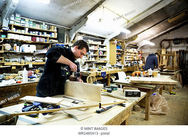 Man standing at a work bench in a carpentry workshop, working on a piece of wood, using a drill