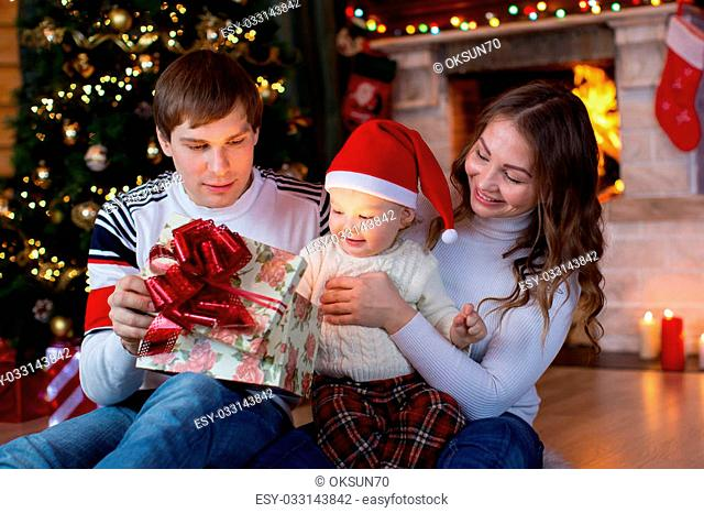 Happy family opening Christmas gift sitting in decorated living room