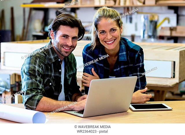 Male and female carpenters using laptop in workshop