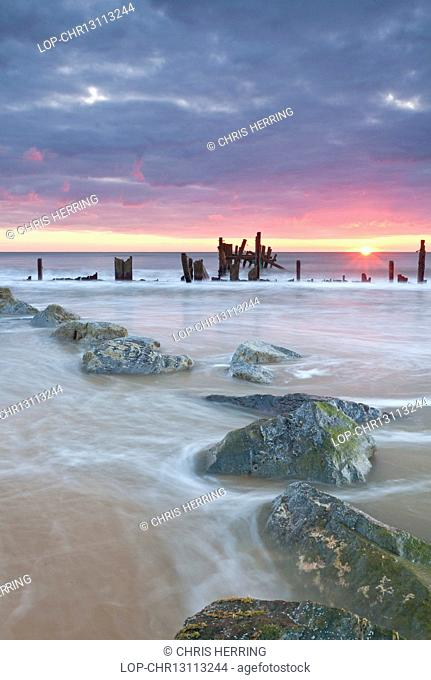 England, Norfolk, Happisburgh. Happisburgh beach and the derelict sea defences at sunrise on the Norfolk coast