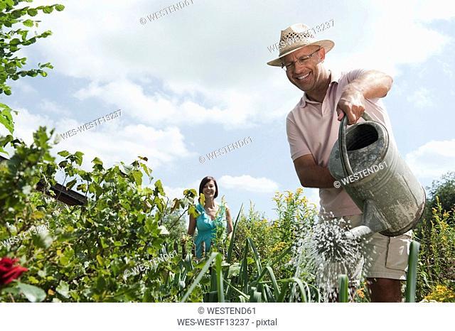 Germany, Bavaria, Senior man watering flowers, woman in background