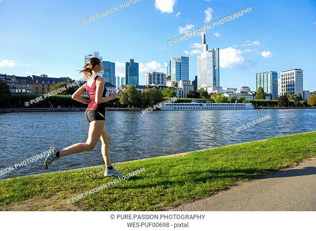 Germany, Frankfurt, young woman running at riverside