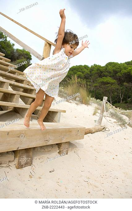 Almost 3 years old little girl jumping from a stair on a beach in Menorca, Spain