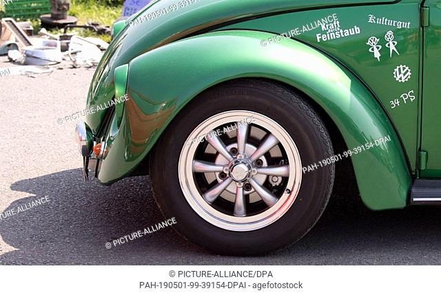 """01 May 2019, Lower Saxony, Hanover: A VW Beetle with the inscription """"""""Kraft durch Feinstaub"""""""" stands at the 36th """"""""Maikäfertreffen"""""""" on a fair parking lot"""