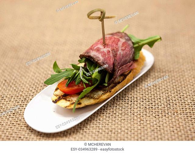 Fresh delicious Spanish tapas with roast beef on the textiles background . Great background for restaurant, cafe
