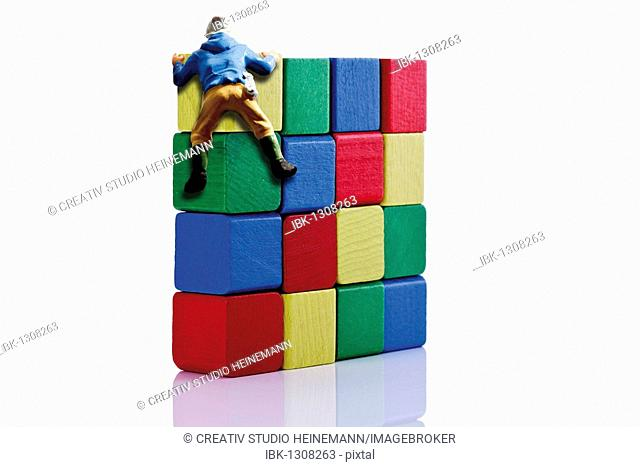 Climber figurine on a wall made of building bricks