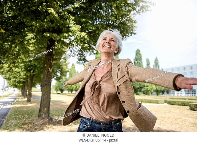 Happy senior woman with outstretched arms in a park