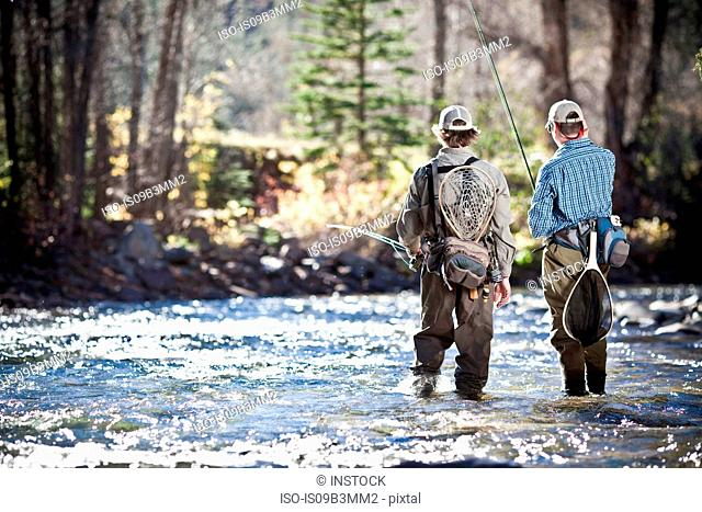 Fishermen ankle deep in river fly fishing, Colorado, USA