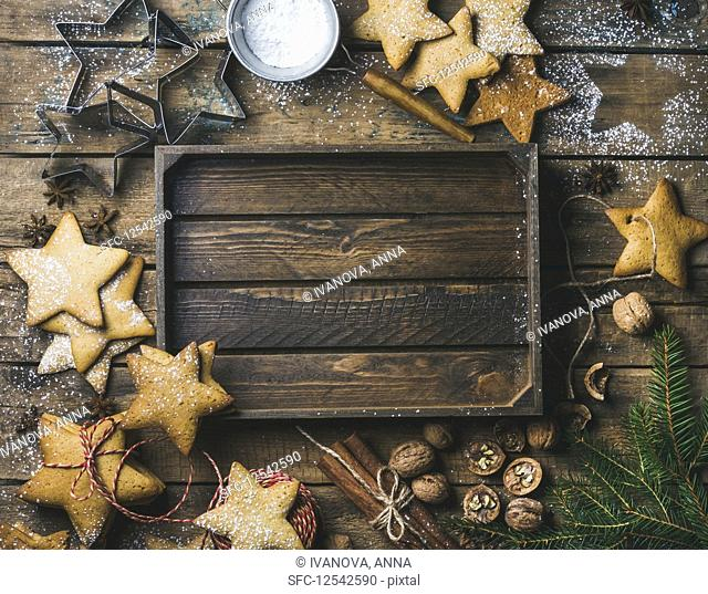 Gingerbread cookies, sugar powder, nuts, spices, baking molds, fir-tree branch, decorative rope on wooden background
