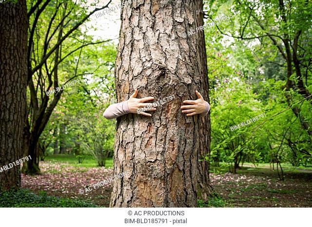 Caucasian woman hugging tree in park