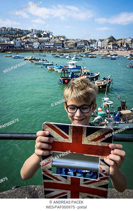 UK, Cornwall, smiling boy taking a selfie at St Ives with his digital tablet
