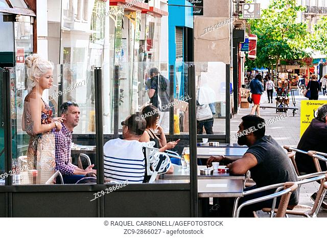 People sitting and talking at cafe terrace. Nantes, Brittany, France