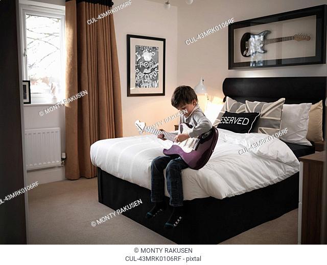 Boy playing guitar in bedroom