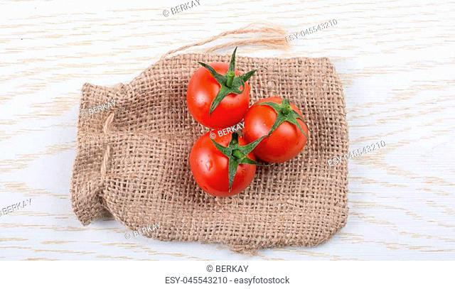 Little canvas sack and red ripe tasty fresh cherry tomatos