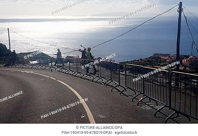 HANDOUT - 18 April 2019, Portugal, Canico: Men are repairing a power line on a road where a serious bus accident occurred the day before on the Portuguese...