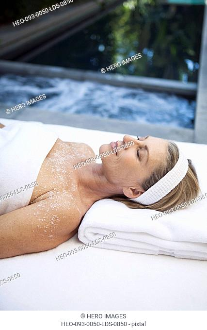 middle aged woman enjoying salt scrub treatment