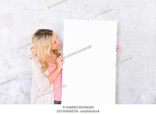 beautiful blond woman is holding white card for copy space
