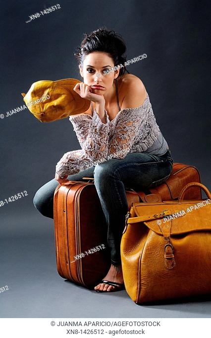 Young woman posing, sitting in a studio with two suitcases of leather and leather yellow cap, looking straight at the camera with the face of boredom