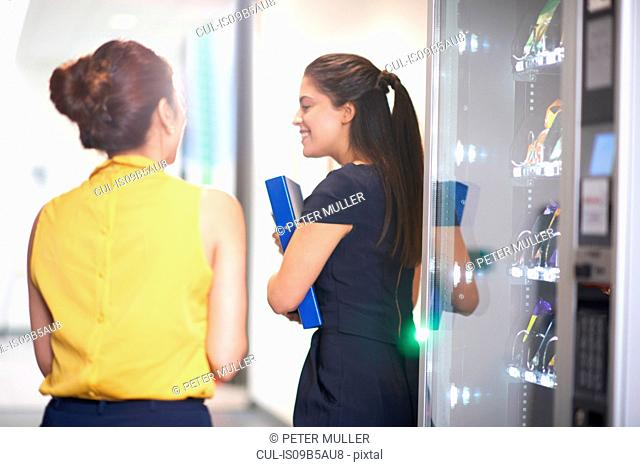 Colleagues chatting by vending machine