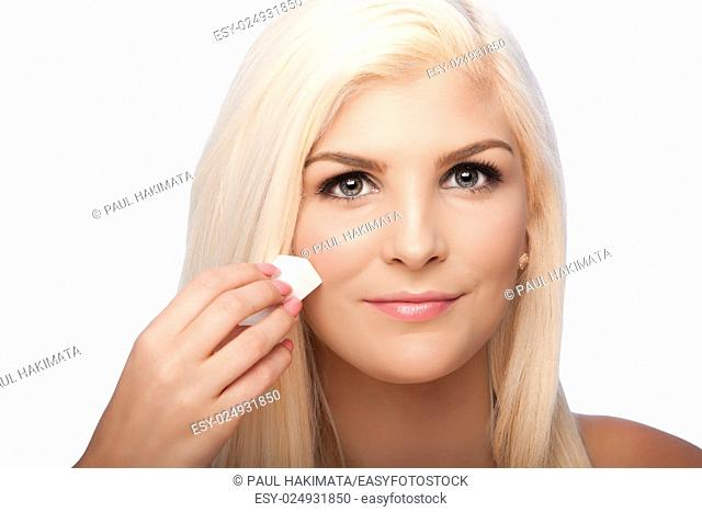 Beautiful face of young woman for Aesthetics facial skincare concept wiping applying makeup cosmetics, on white