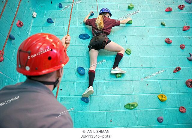 High school student holding rope supporting classmate climbing rock climbing wall
