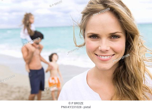 Woman smiling with her family in the background